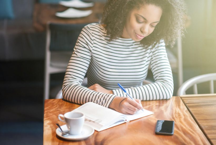 Woman writing in her planner next to cup of coffee